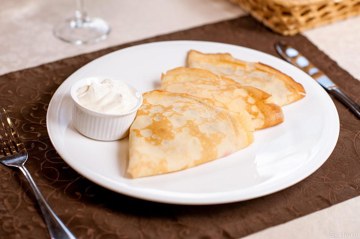 блины со сметаной на белой тарелке